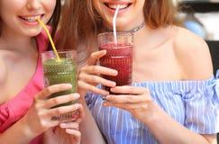 Deux dames attirantes appréciant le smoothie frais Photographie stock