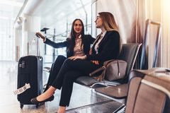 Deux dames d'affaires attendant le vol dans le terminal d'international d'aéroport Image libre de droits