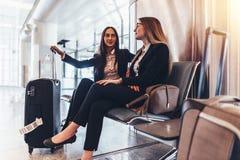 Deux dames d'affaires attendant le vol dans le terminal d'international d'aéroport Image libre de droits