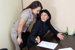 Deux dames d'affaires dans parler de bureau Photos stock