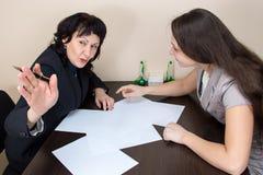 Deux dames d'affaires s'asseyant le bureau et en parlant Image libre de droits