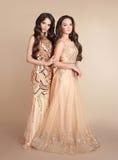 Deux dames de mode Les belles femmes avec les cheveux onduleux porte dedans longtemps Images libres de droits
