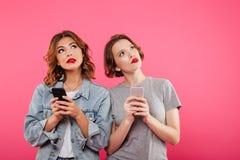 Deux dames de pensée causant par des téléphones Image libre de droits