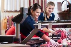Deux dames de ventes dans la boucherie bourrant l'affichage de viande images libres de droits