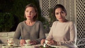Deux dames offensées s'asseyant en café, non disposé à faire des excuses et communiquer images stock