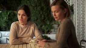 Deux dames tristes s'asseyant dehors après querelle, problème de transmission, conflit photos libres de droits