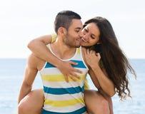 Deux de sourire ayant la date sur la plage sablonneuse Photo stock