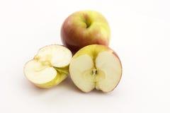 Deux demi pommes et pomme entière ont découpé le ‹en tranches d'†de ‹d'†sur un fond blanc Image libre de droits