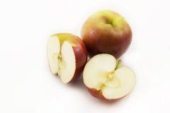 Deux demi pommes et pomme entière ont découpé le ‹en tranches d'†de ‹d'†sur un fond blanc Photo libre de droits