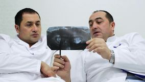 Deux dentistes discutent le r?gime th?rapeutique du patient utilisant un rayon X de la m?choire clips vidéos