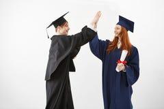Deux diplômés d'université heureux donnant la haute cinq souriant après avoir reçu des diplômes bientôt pour être avocats au-dess Image stock