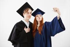 Deux diplômés heureux d'université dupant faisant le selfie au-dessus du fond blanc Photo stock