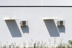 Deux dispositifs climatiques d'extérieurs et leurs longues ombres sur un mur blanc de maison, sous un jour ensoleillé d'été chaud Photo libre de droits
