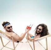 Deux divers types se reposant ensemble sur la plage Photos libres de droits