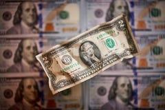 Deux dollars chiffonnés sur un fond brouillé des factures en valeur cent dollars la nouvelle facture américaine photos libres de droits