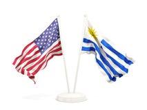 Deux drapeaux de ondulation des Etats-Unis et de l'Uruguay d'isolement sur le blanc illustration stock
