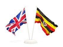 Deux drapeaux de ondulation du R-U et de l'Ouganda d'isolement sur le blanc illustration stock