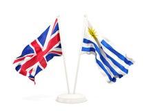 Deux drapeaux de ondulation du R-U et de l'Uruguay d'isolement sur le blanc illustration libre de droits