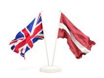 Deux drapeaux de ondulation du R-U et de la Lettonie d'isolement sur le blanc illustration stock