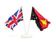Deux drapeaux de ondulation du R-U et de la Papouasie-Nouvelle-Guinée d'isolement sur le blanc illustration stock