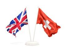 Deux drapeaux de ondulation du R-U et de la Suisse photographie stock