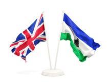 Deux drapeaux de ondulation du R-U et du Lesotho d'isolement sur le blanc illustration stock