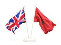 Deux drapeaux de ondulation du R-U et du Maroc d'isolement sur le blanc illustration libre de droits