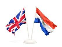 Deux drapeaux de ondulation du R-U et du Paraguay d'isolement sur le blanc illustration stock