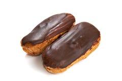 Deux eclairs avec la glaçure de chocolat ont isolé photos libres de droits