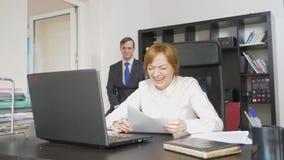 Deux employés de bureau s'asseyent au bureau, une femme travaille sur l'ordinateur, un homme est près Ils rient photo stock