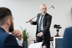 Deux employés sont venus au bureau du ` s de directeur tandis qu'il jouait le golf Il crie à eux Photos stock