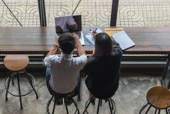 Deux employés travaillant sur l'ordinateur portable image stock