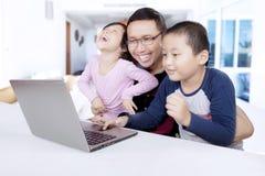 Deux enfants à l'aide d'un ordinateur portable avec leur père photos libres de droits