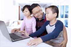 Deux enfants à l'aide d'un ordinateur portable avec leur père Images libres de droits