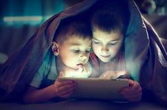 Deux enfants à l'aide du PC de comprimé la nuit photographie stock libre de droits