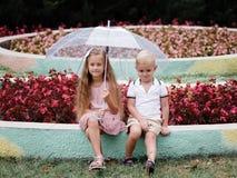 Deux enfants à la mode sous un parapluie en été se garent Marchez un jour pluvieux dans un jardin de fleurs Copiez l'espace photo stock