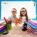 Deux enfants à la table dans la salle de classe sur la leçon Photographie stock libre de droits