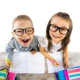 Deux enfants à la table dans la salle de classe sur la leçon Photos stock