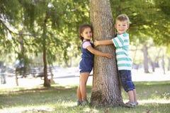 Deux enfants étreignant l'arbre en parc Images stock