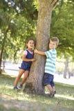 Deux enfants étreignant l'arbre en parc Image libre de droits