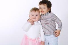 Deux enfants étreignants mignons sur le blanc Images stock