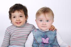 Deux enfants étreignants mignons sur le blanc Image stock