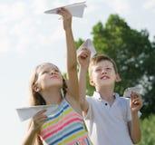 Deux enfants admiratifs jouant avec les avions de papier simples Photographie stock