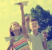 Deux enfants admiratifs jouant avec les avions de papier simples Photo libre de droits