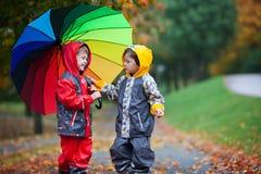 Deux enfants adorables, frères de garçon, jouant en parc avec l'umbrel Photographie stock
