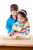 Deux enfants adorables lisant le livre Images stock
