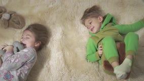 Deux enfants adorables roulant sur le tapis pelucheux Le frère et la soeur ont un amusement Week-end heureux d'enfants banque de vidéos