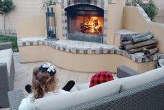 Deux enfants appréciant la chaleur d'un feu d'arrière-cour images libres de droits