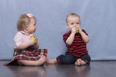 Deux enfants assez petits mangeant des pommes Images libres de droits