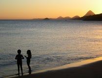 Deux enfants au coucher du soleil Images stock